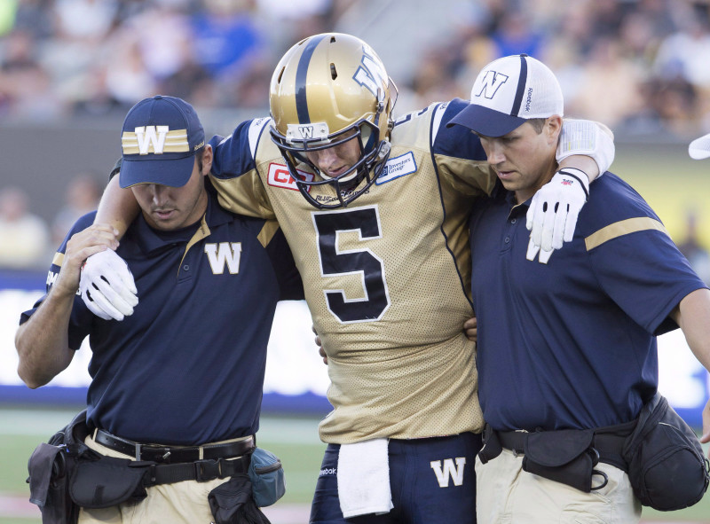 Winnipeg Blue Bombers' Drew Willy, centre, is assisted off of the field after being injured during the second half of CFL football action in Hamilton, Ont., on Sunday, August 9, 2015. The Hamilton Tiger-Cats defeated the Winnipeg Blue Bombers 38-8. THE CANADIAN PRESS/Peter Power